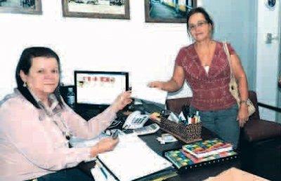 Secretária de Administração, Tânia Gabriel, entrega o novo cartão à servidora