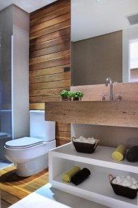 Nesse banheiro as toalhas são apoiadas no móvel sob a bancada. Os detalhes criados pela textura da bancada e onde tem o vaso sanitário dão um charme e um toque acolhedor.