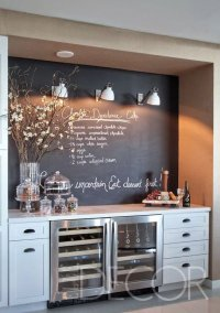 Esta cozinha despojada tem uma bancada com adega, pintura de quadro negro e bancada com petiscos.